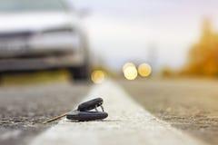 Chiavi perse dell'automobile sugli aghi caduti dell'abete rosso blu bokeh posteriore del fondo della sfuocatura immagine stock libera da diritti