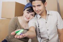 Chiavi romantiche della tenuta delle coppie alla loro nuova casa fotografia stock libera da diritti
