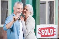 Chiavi senior della tenuta delle coppie della loro nuova casa e di abbracciare sul portico fotografie stock