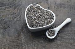 Chiazaden in een witte hart gevormde kom op oude houten achtergrond De zaden van Salviahispanica Stock Foto's
