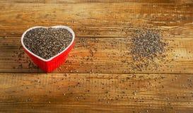 Chiazaden in hart gevormde kom op een rustieke houten lijst Stock Afbeelding