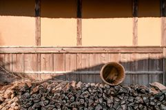 Pile of Firewood at Boso No Mura Open air museum, Chiba, Japan. Chiba, JAPAN - Pile of firewood and wooden bucket at old vintage cottage at Boso No Mura Open air stock image