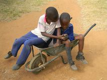 African kids browsing celllphone whilst in wheelbarrow. Chibero,Zimbabwe,May 10 2016.Two primary schoolboys sharing and browsing a cellphone whilst seated in a royalty free stock photo