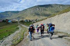 Chibi, Altai Republicl, Russia, augusta, 18, 2016 Turisti che scalano su una strada non asfaltata dal villaggio Chibit a Mazhoysk Fotografia Stock Libera da Diritti