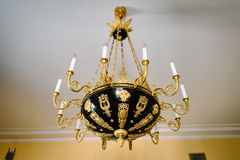 Chic antique black and gold chandelier on the ceiling royalty free stock images