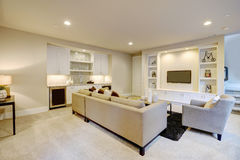 Chic basement living room with wet bar. Chic basement features a gray sectional facing a white built-in tv cabinet and wet bar mounted to a wall. Northwest, USA Stock Photo