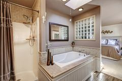 Chic bathroom with luxury drop-in tub. Chic bathroom with modern spa-like drop-in tub with natural stone tile surround and shower with brown shower curtain royalty free stock images