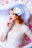 Chic broad-brimmed hat. Portrait of a beautiful bride woman in elegant lace dress and broad-brimmed hat posing over floral background. Wedding. Beauty, fashion stock images