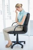 Chic businesswoman sitting exhausted on her swivel chair Stock Photo
