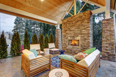 Chic covered back patio with built in gas fireplace. Stone pillars, plank vaulted ceiling over cozy teak wood sofa set topped with white cushions and green Royalty Free Stock Photography