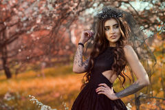 Chic dark-haired tattooed young woman wearing lace dress and black jewel crown with veil standing in the autumn garden Royalty Free Stock Image