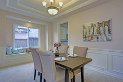 Chic dining room accented with wall panel mouldings and tray ceiling. Chic dining room with light grey walls accented with wall panel mouldings under tray royalty free stock image