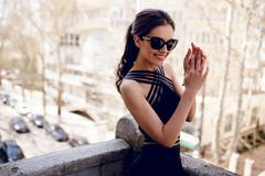 A chic, elegant brunette in black sunglasses, sexy black dress, hair ponytail, smiles with hands close to face. stock photo
