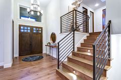 Chic entrance foyer with high ceiling and white walls. Chic entrance foyer with high ceiling and wide staircase with lights and contemporary railing. New Custom stock photos