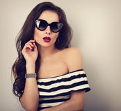 Chic female model with long hair posing in fashion sunglasses in Royalty Free Stock Image