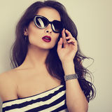 Chic female model with long hair posing in fashion sunglasses in. Striped dress with hand near face. Toned color closeup portrait stock image