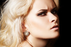Chic frown model with diamond jewelry, blond hair. Fashionable close-up portrait of glamour woman model with sexy evening make-up & chic shiny jewellery Stock Photography