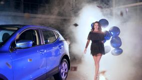 Chic girl with inflatable balloons stands near car in smoke among flying confetti. Chic girl in black dress with inflatable balloons stands near car in smoke stock video footage