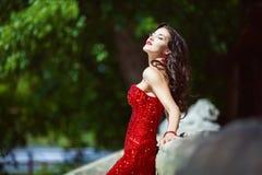 Chic kvinna med mörkt lockigt långt hår i röd klänning Fotografering för Bildbyråer