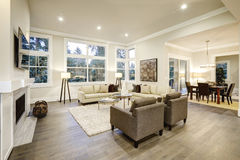 Chic light living room design with dark floors. Furnished with glass top accent tables and beige sofas topped with brown pillows . Northwest, USA Royalty Free Stock Photos