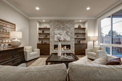 Chic living room interior in gray colors. Living room interior in gray and brown colors features stone fireplace with built-in shelves and cabinets, large dark Stock Photo