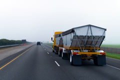 Chic new yellow truck with two bulk trailers on straight as arrow highway in fog. Modern bright yellow semi truck with two conical trailers for bulk cargoes royalty free stock image