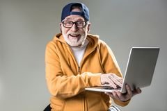Chic old man deriving pleasure from technology royalty free stock photography