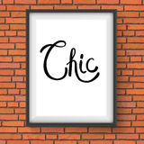 Chic Text in a White Frame Hanging on Brick Wall Stock Image