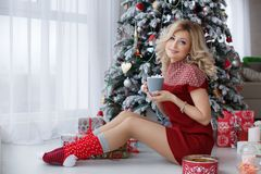 Beautiful woman near a Christmas tree with a cup of coffee with marshmallows. A chic woman, a beautiful blonde with long wavy hair and blue eyes, dressed in a Royalty Free Stock Image