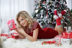 Beautiful woman near a Christmas tree with a cup of coffee with marshmallows. A chic woman, a beautiful blonde with long wavy hair and blue eyes, dressed in a Stock Photos