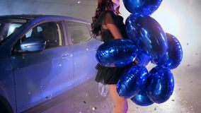Chic woman in black dress with vivid balloons into arms dancing in sparkles at automobile parking into smoke. Chic woman in black dress with vivid balloons into stock video