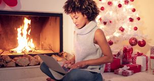 Chic young woman typing a Christmas message. On her laptop computer as she relaxes in front of the tree and a heap of gifts alongside a burning warm fire stock video