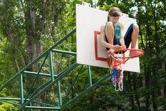 Chica joven ágil que fija una red en una meta del baloncesto Fotografía de archivo