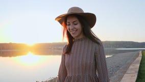 Chica joven adorable con la presentación sonriente del sombrero en la cámara cerca del lago almacen de video