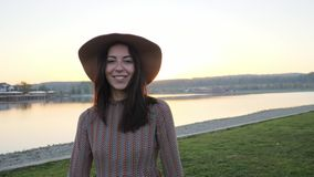 Chica joven adorable con la presentación sonriente del sombrero en la cámara cerca del lago almacen de metraje de vídeo