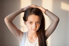 Chica joven adorable que hace su pelo con ambas manos Imágenes de archivo libres de regalías