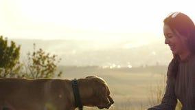 Chica joven adorable que juega con el perro y que lo alimenta en la naturaleza metrajes