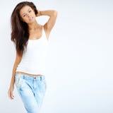 Chica joven adorable que presenta en la camisa blanca Foto de archivo