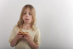 Chica joven adorable que presenta la consumición malsana con un cheesebur Fotos de archivo