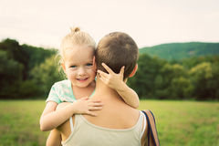 Chica joven adorable que sonríe y que abraza a su madre Imagen de archivo libre de regalías