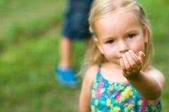 Chica joven adorable que sostiene el saltamontes Fotos de archivo libres de regalías
