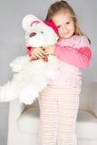 Chica joven agradable en color de rosa en fondo ligero Imagen de archivo