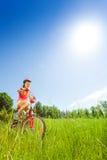 Chica joven agradable que se sienta en una bici Imagen de archivo
