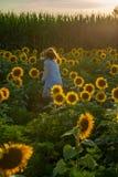 Chica joven alegre de la belleza con el girasol que disfruta de la naturaleza y que ríe en campo del girasol del verano Sunflare, imagenes de archivo