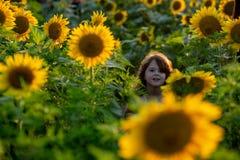 Chica joven alegre de la belleza con el girasol que disfruta de la naturaleza y que ríe en campo del girasol del verano Sunflare, fotos de archivo libres de regalías