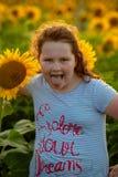 Chica joven alegre de la belleza con el girasol que disfruta de la naturaleza y que ríe en campo del girasol del verano Sunflare, fotografía de archivo