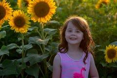 Chica joven alegre de la belleza con el girasol que disfruta de la naturaleza y que ríe en campo del girasol del verano Sunflare, Foto de archivo