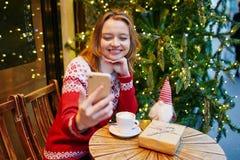 Chica joven alegre en suéter del día de fiesta en el café adornado para la Navidad imagen de archivo
