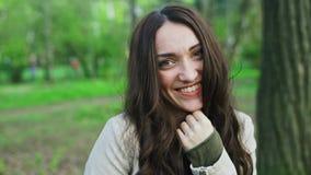 Chica joven alegre hermosa que mira la cámara y la sonrisa metrajes