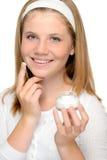 Chica joven alegre que aplica la crema de cara del moistuizer Imagen de archivo